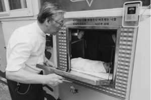 Pastor Lee checks the drop box to find an abandoned infant (from the film)